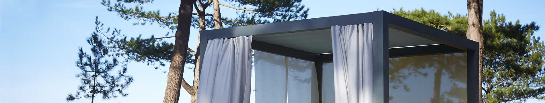 A pergola with Dickson curtains, gray tensioned fabric and side awnings